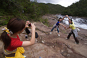 Iriomote-jima. Tourists exploring the forests along Urauchi-gawa (river). Taking souvenir photo at Mariyudo?-no-taki (waterfalls).