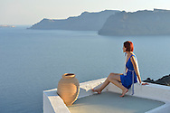 Woman in blue dress in Oia,Santorini, Kyclades,South Aegean, Greece,Europe<br /> Model release 0343