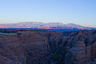 The sandstone cliffs of Arches National Park as seen from the Gemini Bridges area near Moab, UT at sunset