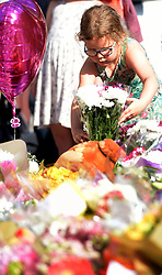 A young girls places flowers during a vigil at St Ann's Square in Manchester, after a suicide bomber killed 22 people leaving a pop concert at the Manchester Arena on Monday night.