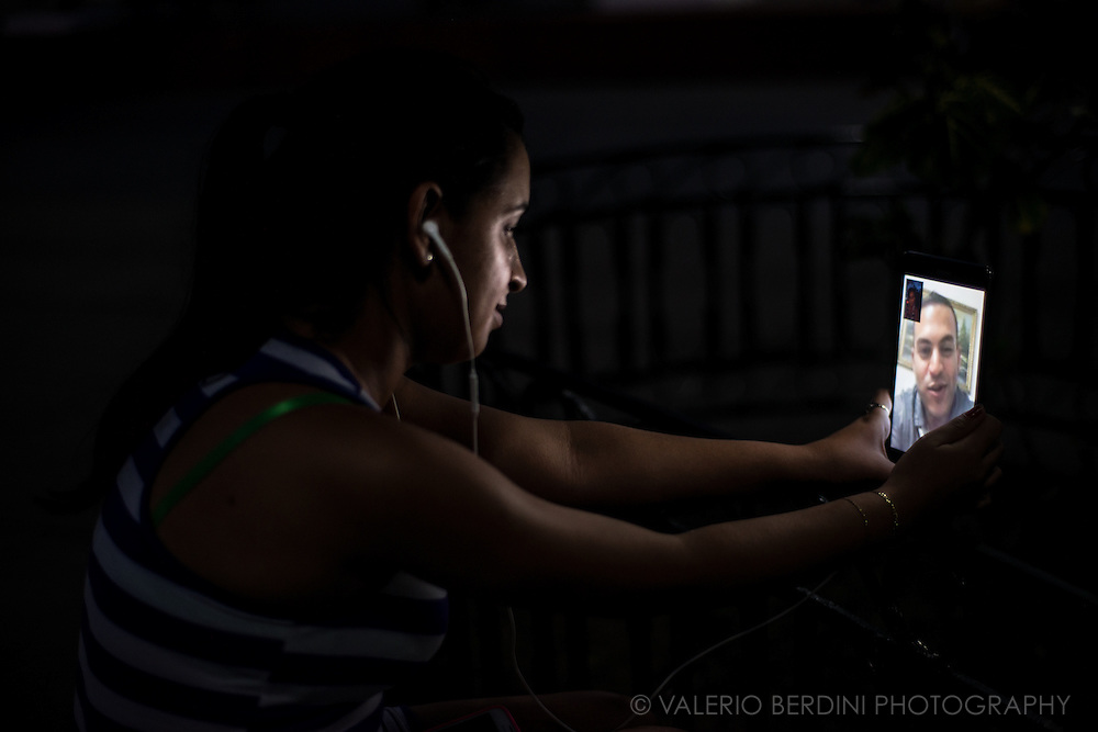 A woman stares at her partner on a tablet during a videocall in Plaza Carillo, Trinidad de Cuba on the afternoon of 26 December 2015. For the first time since the arrive of wi-fi in the last few months, Cuban have seen their loved ones for the first time. Videocall services as Skype and Facetime are blocked by the government; most Cubans use an app called IMO to connect with relatives and friend living abroad, mainly in Florida, Venezuela and Spain. This woman was aware of the photographer, but she continued on her call. This photo was not staged.