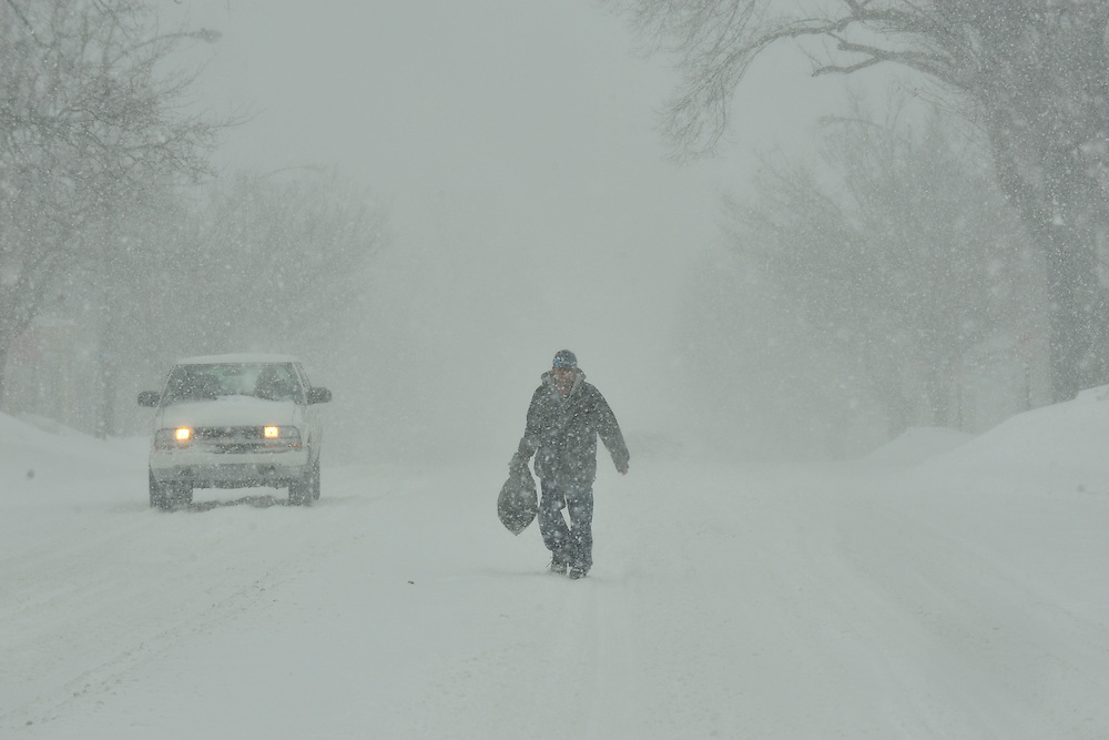 A man walks through deep snow and blizzard conditions delivering on Broad Street Thursday, Feb. 13, 2014 in Bethlehem, PA. (AP Photo/Chris Post)