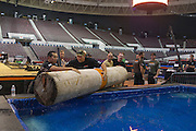 Contestants and stage crew put a log in a pool for the log-roll portion of the Stihl Timbersports Championships at The Norfolk Scope in Norfolk, Virginia while preparing for the event on June 19, 2014.