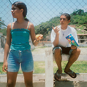 Two teenagers standing by a concrete fence, the boy eating a bag of sweets/crisps, Brazil