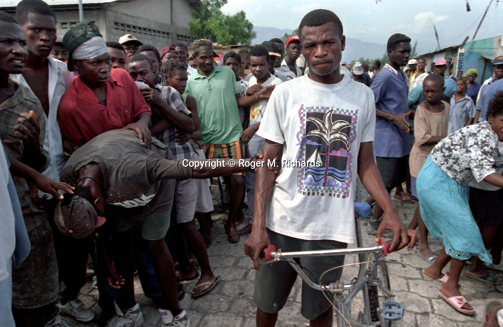 "A man who was accused of stealing a bicycle is held by a lynch mob in the poor neighborhood of Cite Soleil  in Port-au-Prince, Haiti, May 1995. The man was thrown into the back of a pickup truck and driven away to face what some members of the mob called 'street justice"". The accused thief's fate is unknown. (Photo by Roger M. Richards)"