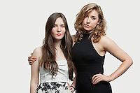Portrait of two young female friends standing together over gray background