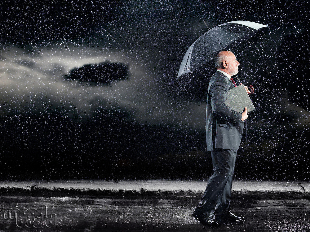 Businessman Walking in rain under umbrella side view