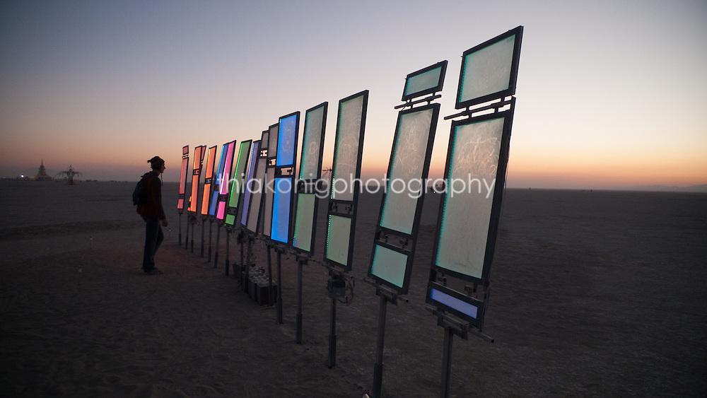 Man looks at solar illuminated art installation at dawn, Black Rock desert, during Burning Man Festival.