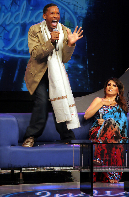 Hollywood actor and Grammy award winner Will Smith shows how he relieves his nervousness prior to facing cameras for movie shots, as Indian television personality Mini Mathur (R) looks on at the sets of a television reality show in Mumbai, February 24, 2006. Smith is in India to promote a private entertainment channel and has been discussing possible joint ventures with Bollywood filmmakers.REUTERS/Prashanth Vishwanathan
