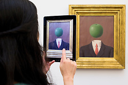 © Licensed to London News Pictures. 14/06/2013. London, UK. A Sotheby's employee uses an iPad to take a picture of L'Idee' (1966, est. GB£1,800,000-2,500,000) by French surrealist Rene Magritte at the press view for a Sotheby's auction in London today (14/06/2013). The Impressionist and Modern Art Evening Sale takes place on the 19th of June 2013 at Sotheby's New Bond Street premises.  Photo credit: Matt Cetti-Roberts/LNP