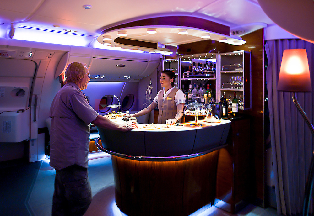 Emirates A380 business class upper deck bar during overnight flight to Dubai with passenger and female flight attendant chatting talking over drinks and refreshments.