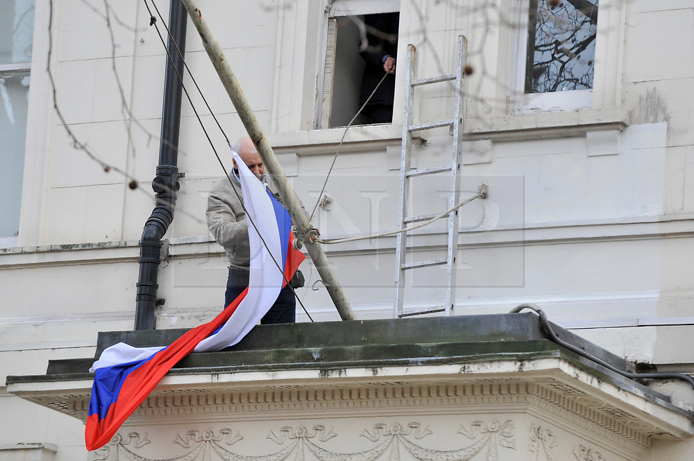 © Licensed to London News Pictures. 14/03/2018. LONDON, UK.  A workman replaces a damaged flag displayed outside the Embassy of Russia in Kensington.  Britain has given 23 Russian diplomats a week to leave the country following the attack on ex-spy Sergei Skripal and his daughter Yulia with nerve gas in Salisbury..  Photo credit: Stephen Chung/LNP