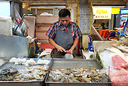 A man descales fish inside the Or Tor Kor market in Bangkok Thailand.