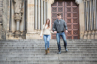 Full length of young couple moving down steps against building