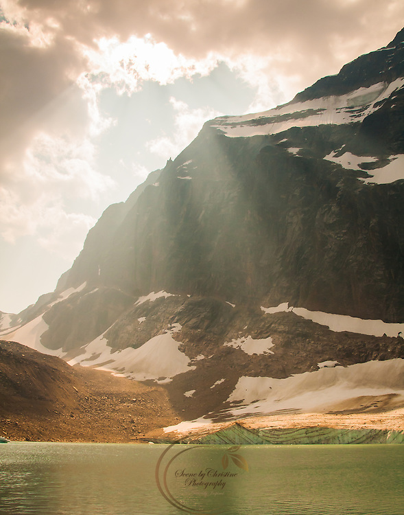 Sunlight streams through the clouds onto a small lake bordering Cavell Glacier in Jasper National Park.