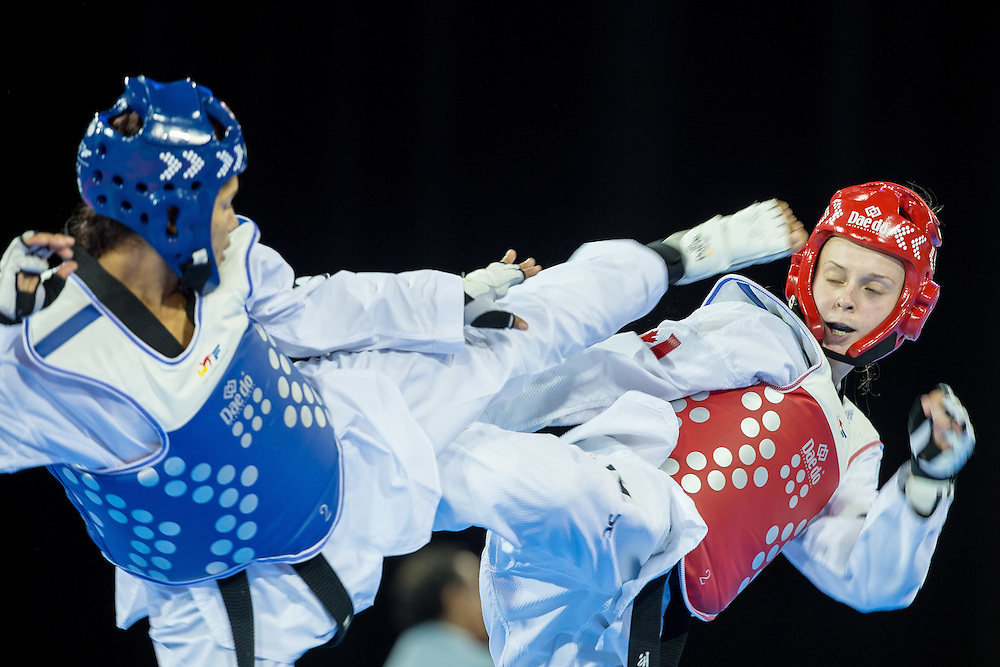 Evelyn Gonda of Canada and Disnansi Polanco of the Dominican Republic trade kicks during their 1/8 round contest in the -57kg weight class of Taekwondo at the 2015 Pan American Games in Toronto, Canada, July 20,  2015.  AFP PHOTO/GEOFF ROBINS