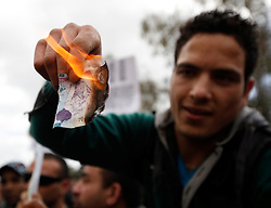 A protestor burns a Libyan dinar bill featuring the face of Libyan leader Muammar Gaddafi during a protest outside the Libyan Embassy in Attard, outside Valletta, February 22, 2011. The protest was organised by the Libyan community living in Malta against the Libyan government's crackdown on demonstrators in Libya..Photo by Darrin Zammit Lupi
