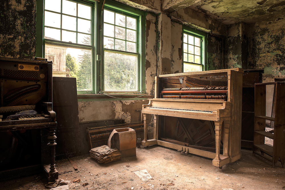 An old Merrill 1934 piano sits in the dust and decay of an old state poorhouse in NY.