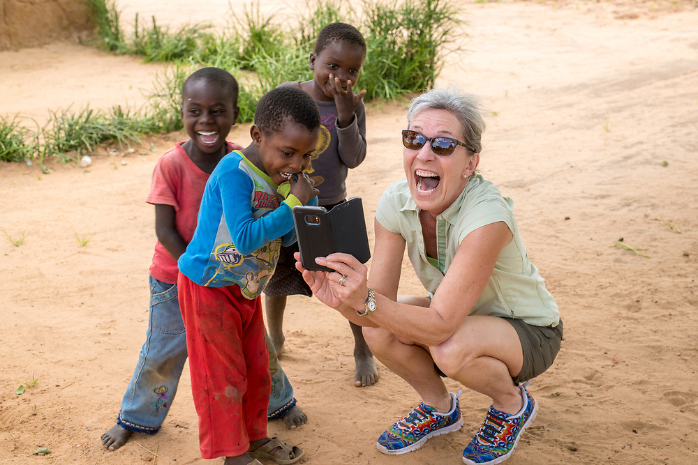 A woman excitedly shares something on her phone with a group of young boys. Livingstone, Zambia