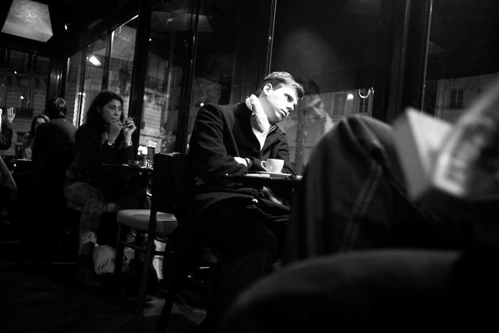 A man waits in a Parisian cafe on a winter's night.