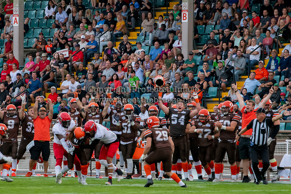 KELOWNA, BC - AUGUST 17:  Brycen Mayoh #4 and Nathan Falito #1 of Westshore Rebels tackle Nate Adams #41 of Okanagan Sun after he intercepts the ball in front of the Okanagan Sun team bench at the Apple Bowl on August 17, 2019 in Kelowna, Canada. (Photo by Marissa Baecker/Shoot the Breeze)