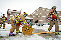 Kootenai County firefighters clear equipment from the area outside The Arena at Post Falls High School after extinguishing a dryer fire Tuesday morning. Students were released from school for the day after being sent to Prairie View Elementary and Real Life Ministries during the evacuation due to heavy smoke.