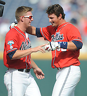 Mississippi's J.B. Woodman (12) hands a baseball to Mississippi's John Gatlin (36) following Gatlin's game winning hit against Texas Tech at T.D. Ameritrade Park in the College World Series in Omaha, Neb. on Tuesday, June 17, 2014. Ole Miss won 2-1.
