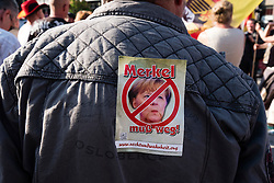 "Far-right demonstrators protest against Islam, refugees and Angela Merkel in Berlin. Sign says ""Merkel must go""."