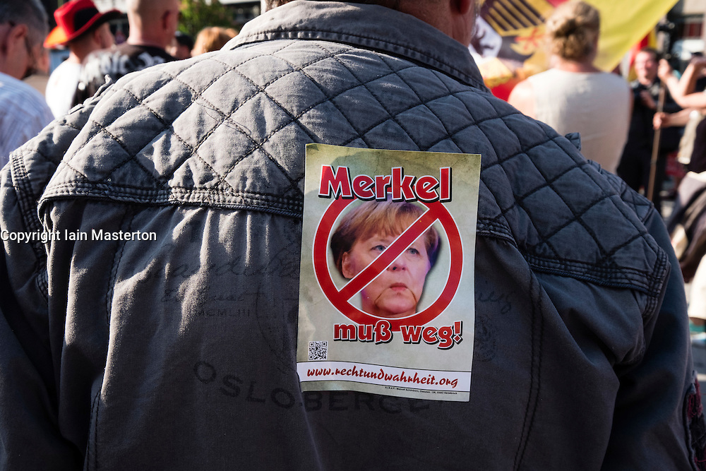 "Far-right demonstrators protest against Islam, refugees and Angela Merkel in Berlin. Sign says ""Merkel must go""."