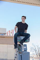 young man sitting on an abandoned gas pump in New Mexico
