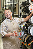 Happy mature salesperson standing by electrical wire spool while looking away in hardware store