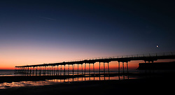 © Licensed to London News Pictures.12/06/15<br /> Saltburn by the Sea, England<br /> <br /> A crescent moon and an aircraft con trail are seen in the morning sky as dawn breaks over the pier at Saltburn by the Sea.<br /> <br /> Photo credit : Ian Forsyth/LNP