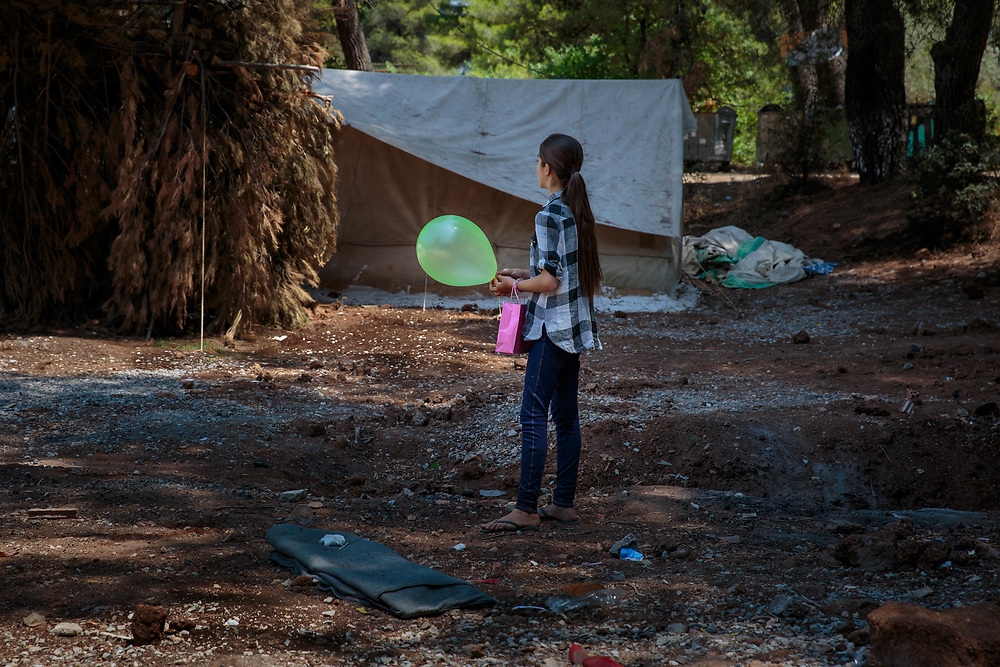 A young refugee from Aleppo, Syria holds her Eid Al Fitr balloon and gift bag distributed by an INGO in Ritsona refugee camp, an hour north of Athens, Greece. July 2016.<br />
