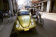"""Glänzender goldfarbener VW-""""Käfer"""" zieht die Blicke eines vorbeiradelnden Rikscha-Fahrers in der Altstadt der kubanischen Metropole Havanna auf sich"""