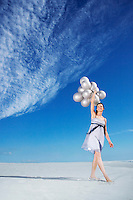 Woman holding balloons on beach