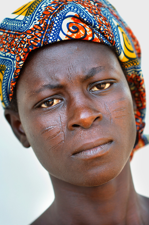 Benin, Abomey-Calavi November 24, 2006 - Woman with tribal scarification on her face. Scarification is used as a form of initiation into adulthood, beauty and a sign of a village, tribe, and clan.