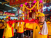 """02 JUNE 2017 - SAMUT SAKHON, THAILAND:  Men prepare to carry the City Pillar Shrine to waiting boats. The Chaopho Lak Mueang Procession (City Pillar Shrine Procession) is a religious festival that takes place in June in front of city hall in Samut Sakhon. The """"Chaopho Lak Mueang"""" is  placed on a fishing boat and taken across the Tha Chin River from Talat Maha Chai to Tha Chalom in the area of Wat Suwannaram and then paraded through the community before returning to the temple in Samut Sakhon. Samut Sakhon is always known by its historic name of Mahachai.     PHOTO BY JACK KURTZ"""