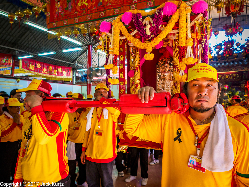 "02 JUNE 2017 - SAMUT SAKHON, THAILAND:  Men prepare to carry the City Pillar Shrine to waiting boats. The Chaopho Lak Mueang Procession (City Pillar Shrine Procession) is a religious festival that takes place in June in front of city hall in Samut Sakhon. The ""Chaopho Lak Mueang"" is  placed on a fishing boat and taken across the Tha Chin River from Talat Maha Chai to Tha Chalom in the area of Wat Suwannaram and then paraded through the community before returning to the temple in Samut Sakhon. Samut Sakhon is always known by its historic name of Mahachai.     PHOTO BY JACK KURTZ"