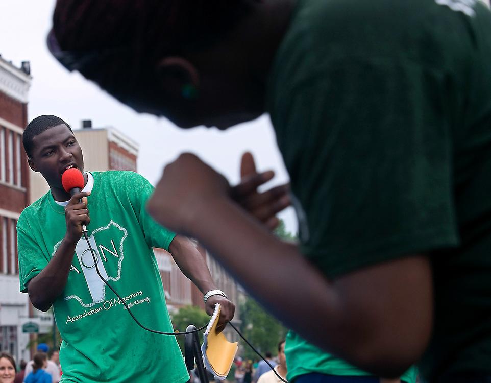 Ayeni Babtope, of the Association of Nigerians, sings a traditional Nigerian song while Yewande Odunaiya, forground, and Wale Omosebi dance during the International Street Fair Saturday.