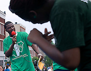 Ayeni Babtope, of the Association of Nigerians, sings a traditional Nigerian song while Yewande Odunaiya, forground, and Wale Omosebi dance during the International Street Fair Saturday.