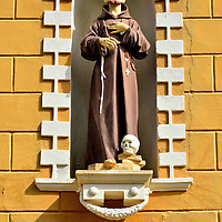 Monk Statue With Skull in Niche in Kralendijk, Bonaire <br /> This monk statue with a skull at his feet originally adorned the St. Franciscus convent for the Sisters of Roosendaal. This building, called the Sentro di Salu Convent, now houses the management and administrative offices of Fundashon Mariadal along with their home care facilities. This foundation also operates a nursing home, a hospital and provides other medical services. The organization employs over 500 people.