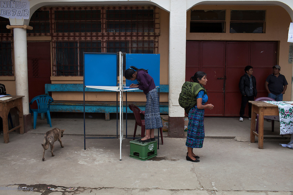 A girl stands on a plastic crate as she votes during the community consultation on extractive and energy industries in Santa Maria Chiquimula. Votes from minors under 18 are not counted in the final tally, nevertheless, their participation is valued in the Kiche Mayan community as an exercise in democracy. Since 2005, the consultation processes carried out in indigenous territories in Guatemalan are considered a preventive measure in the struggle to protect indigenous territories and their cultures from industrial projects. Santa Maria Chiquimula, Totonicapan, Guatemala. October 26, 2014.