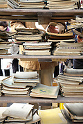 person reading with stacks of old books in front at a flea market