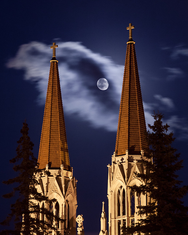 The moon appears between the spires of St. Helena Cathedral in Helena Montana.