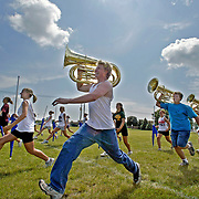 "MOC-Floyd Valley High School band members take extra long strides during a summer band camp rehearsal in August.  A normal marching step is 22 1/2 inches, or 16 steps for every 10 yards. ""If you want to be called a band geek, walk like that in the hallways at school.  You deserve whatever they call you,"" director Steve Connell jokingly told his band.  ""But out here, that's a marching step.""  photo by david peterson"