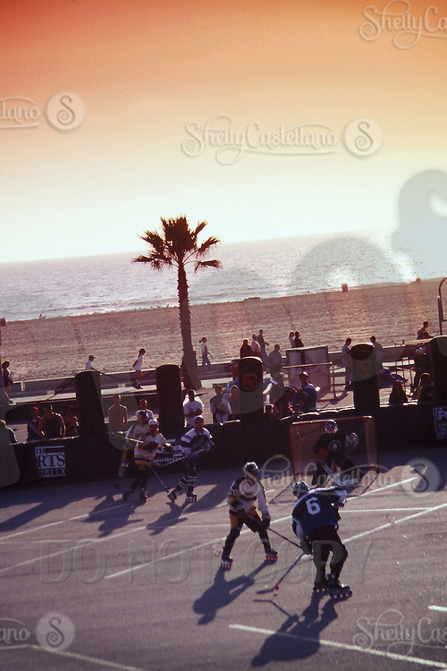 1998:  Player shoots the ball on goal during NHL Breakout grass roots program.  Hockey at the beach in Santa Monica, CA.  Sunshine, outdoor wave crashing on beach in background. Palm Tree along boardwalk.  Southern California summer sport. Transparency slide scan.