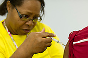Parthenia Harden of the Immunization Collaboration of Tarrant County gives a shot in Fort Worth, Texas on August 30, 2013. The Immunization Collaboration offers low cost vaccines targeting hepatitis, the flu, chickenpox, measles, mumps and HPV amongst other illnesses. (Cooper Neill / for The Texas Tribune)