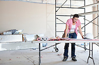 Front view of young female contractor looking at building plans at table