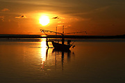 A fisherman pulls his boat at sunrise near the Nora Beach Resort, Koh Samui, Surat Thani, Thailand.
