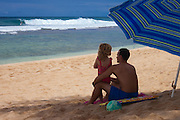 A father and his small daughter gaze out at the surf on the north shore of Oahu in Hawaii